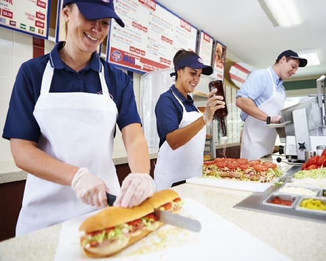 people preparing subs on a table at Jersey Mike's