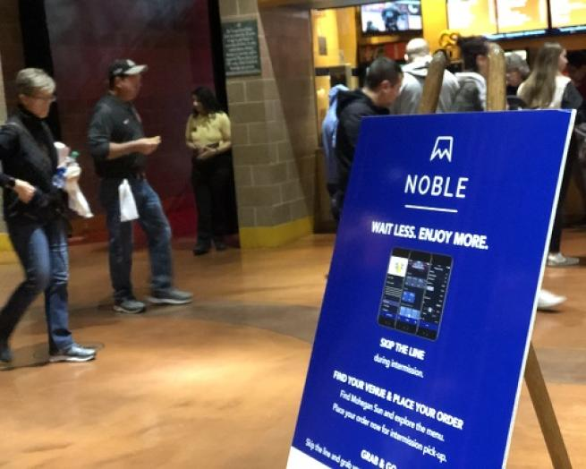 a group of people standing in a room ordering food with Noble