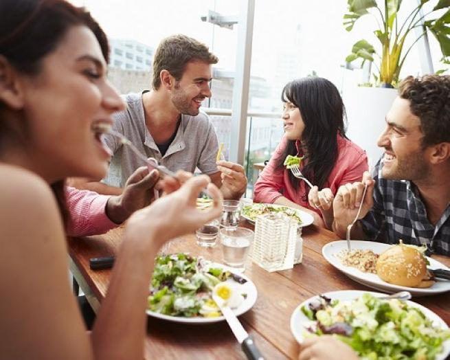 a group of people sitting at a table eating food