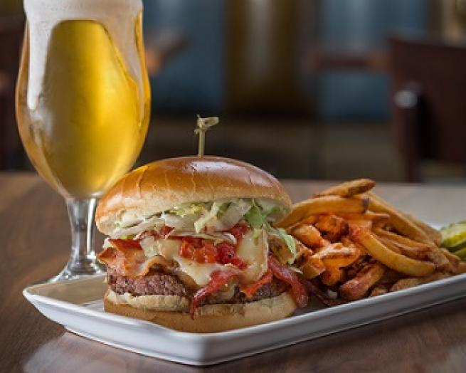 a plate of food and a glass of beer on a table from Bru Burger Indy