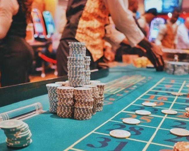 a group of people sitting at a gaming table in a casino