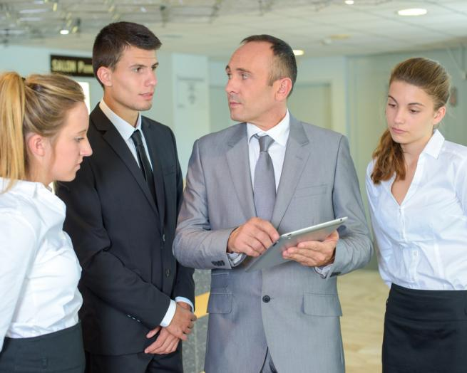 a group of people standing next to a person in a suit and tie