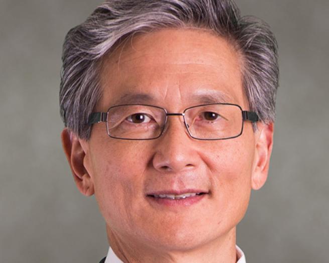 David Kong wearing glasses and smiling at the camera